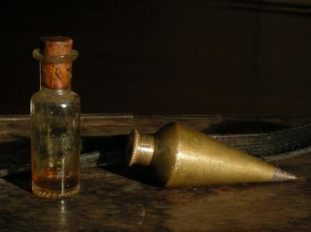 The oil bottle and plumb bob of  the instrument.
